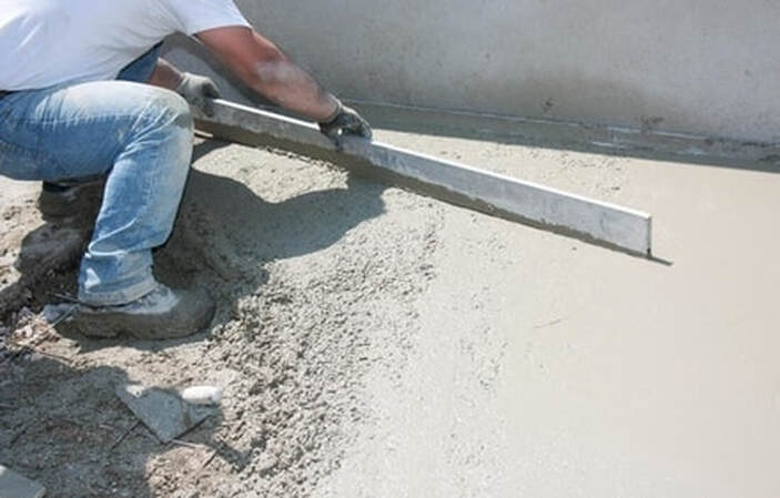 Our crew member preforming concrete service for a client's commercial property.